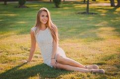 A jovem mulher atrativa senta-se na grama em um parque do verão Fotos de Stock