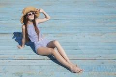 A jovem mulher atrativa toma sol no fundo brilhante Fotografia de Stock