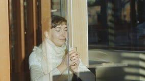 A jovem mulher bebe o café no café Retrato da mulher caucasiano com o lenço de lãs do laço que aprecia o aroma do café que sorri  filme