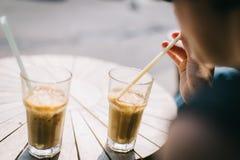 A jovem mulher bebe um café congelado doce fotos de stock