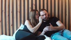 A jovem mulher beija o homem ao mordente, par loving que senta-se na cama Uso masculino o smartphone, fotos das mostras à fêmea filme