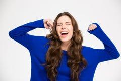 Jovem mulher bem sucedida entusiasmado ectática com mãos levantadas que comemora a vitória Fotografia de Stock Royalty Free