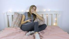 A jovem mulher boceja e comuta os canais de televisão vídeos de arquivo