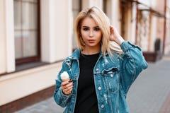 Jovem mulher bonita bonita à moda no vestido elegante da sarja de Nimes do verão com caminhadas doces do gelado em torno da cidad imagens de stock royalty free