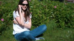 A jovem mulher bonita é de chamada e de fala no telefone celular que senta-se no parque video estoque