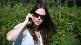 A jovem mulher bonita é de chamada e de fala no telefone celular que senta-se no parque filme