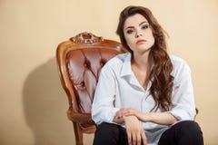 A jovem mulher bonita é situada na cadeira imagem de stock royalty free