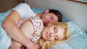A jovem mulher bonita acorda na manhã em que seu homem a abraça