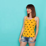 Jovem mulher bonita alegre na observação amarela da camiseta de alças Fotografia de Stock