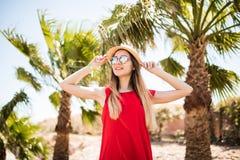 Jovem mulher bonita alegre no vestido e no chapéu vermelhos que anda e que fala no telefone celular no recurso de verão e no fund fotos de stock royalty free