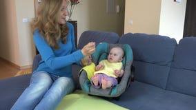 A jovem mulher bonita alimenta o bebê da filha com colher em casa 4K video estoque
