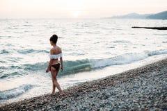 A jovem mulher bonita anda para molhar na praia do mar foto de stock royalty free