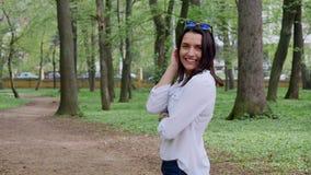A jovem mulher bonita aprecia o parque da cidade, sorri filme