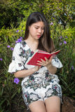 Jovem mulher bonita asiática que lê um livro no jardim exterior imagem de stock