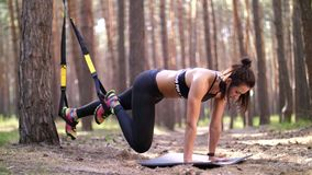 A jovem mulher bonita, atlética, 'sexy', treinador, instrutor, executa os exercícios, fazendo exercita com sistema do trx da apti video estoque