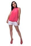 A jovem mulher bonita, atrativa na blusa e o short curto que está no dedos puxando completos pockets Fotografia de Stock