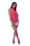 A jovem mulher bonita, atrativa na blusa e os sorrisos curtos do short docemente, puseram sua mão sobre seu comprimento anca, com Fotos de Stock Royalty Free