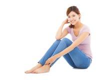 Jovem mulher bonita atrativa que senta-se no assoalho Fotografia de Stock Royalty Free