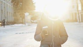 A jovem mulher bonita bebe o café quente de um copo de papel no inverno ensolarado, em uma rua nevado da cidade video estoque