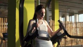 A jovem mulher bonita bombeia acima a imprensa em um fim à moda do gym acima vídeos de arquivo