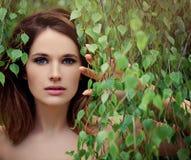 Jovem mulher bonita com as folhas verdes do vidoeiro imagens de stock royalty free