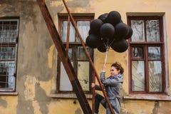 Jovem mulher bonita com balões pretos Imagens de Stock Royalty Free
