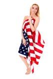 Jovem mulher bonita com a bandeira nacional dos EUA isolada no fundo branco imagem de stock