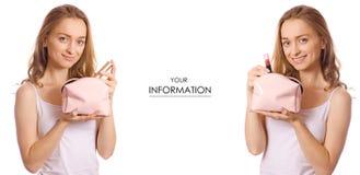 A jovem mulher bonita com batom cosmético do saco da composição e a escova nas mãos ajustaram o teste padrão Foto de Stock