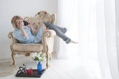 Jovem mulher bonita com a câmera da foto na cadeira confortável grande perto da janela Imagem de Stock