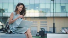 Jovem mulher bonita com câmera que datilografa em seu portátil que senta-se perto do arranha-céus filme