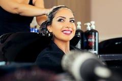 Jovem mulher bonita com cabeça de lavagem do cabeleireiro no cabeleireiro Foto de Stock