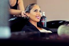 Jovem mulher bonita com cabeça de lavagem do cabeleireiro no cabeleireiro Imagens de Stock
