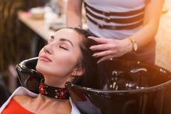 Jovem mulher bonita com cabeça de lavagem do cabeleireiro no cabeleireiro Termas, cuidado, beleza e povos fotografia de stock
