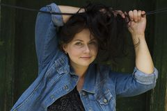 A jovem mulher bonita com cabelo castanho escuro sorri no fundo da madeira do vintage Retrato do modelo fêmea europeu de sorriso  Foto de Stock