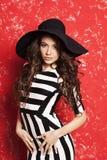 Jovem mulher bonita com cabelo encaracolado longo no chapéu negro e no vestido listrado no fundo vermelho Imagens de Stock