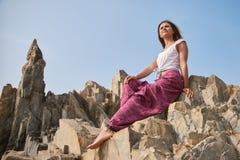 A jovem mulher bonita com cabelo escuro na veste e em calças largas senta-se em uma rocha contra o céu o conceito do resto na est imagem de stock royalty free
