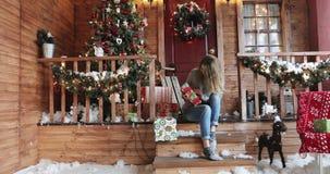 A jovem mulher bonita com cabelo longo examina caixas de presente em um patamar da casa filme