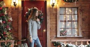 Jovem mulher bonita com cabelo longo que examina o ano novo e as decorações do Natal em um patamar da casa vídeos de arquivo