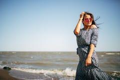 Jovem mulher bonita com cabelo preto em um vestido longo que tem o divertimento na praia do mar de Azov Foto de Stock Royalty Free