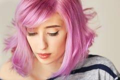 Jovem mulher bonita com cabelo tingido no fundo da cor fotografia de stock