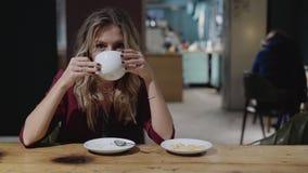 Jovem mulher bonita com café bebendo do cabelo encaracolado, sorrindo e escutando filme