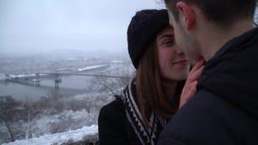 Jovem mulher bonita com cintas dos dentes e homem que olha nos olhos de cada um perto do rio na roupa do inverno feliz filme