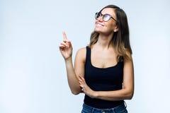 Jovem mulher bonita com exibição dos monóculos e apontar sobre o fundo branco imagem de stock