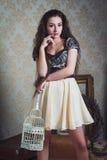 Jovem mulher bonita com a gaiola de pássaros branca Fotografia de Stock Royalty Free