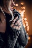 A jovem mulher bonita com mão no bokeh dourado ilumina o backgroun Foto de Stock Royalty Free