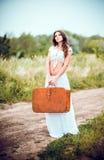 A jovem mulher bonita com a mala de viagem nas mãos está na estrada rural Imagem de Stock Royalty Free
