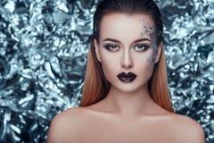 Jovem mulher bonita com nivelamento da composição cintilante no fundo do Natal que olha in camera Imagens de Stock