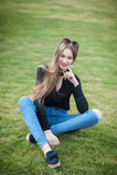 Jovem mulher bonita com o cabelo longo que senta-se na grama verde Fotos de Stock Royalty Free