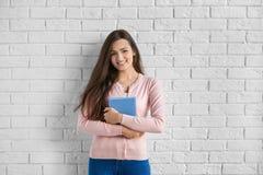 Jovem mulher bonita com o livro que está a parede próxima Fotografia de Stock Royalty Free