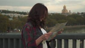 Jovem mulher bonita com o mapa do turista que olha ao redor na rua da cidade video estoque
